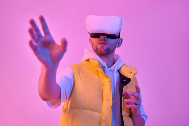 Jonge aantrekkelijke man in vrijetijdskleding, maakt gebruik van virtual reality-bril, probeert iets aan te raken met zijn hand, geïsoleerd op neon roze