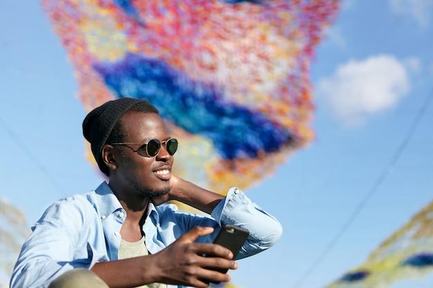 Jonge aantrekkelijke man met donkere huid en haren, het dragen van modieuze kleding en tinten, mobiele telefoon in de hand houden