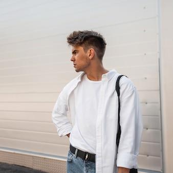Jonge aantrekkelijke man model in een elegant wit overhemd in een t-shirt in blauwe stijlvolle jeans met een vintage tas staat op straat