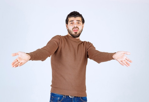 Jonge aantrekkelijke man model permanent en hulpeloos gebaar met arm en handen tonen.