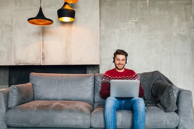 Jonge aantrekkelijke man op sofa thuis in de winter in koptelefoon, luisteren naar muziek, dragen rode gebreide trui, bezig met laptop, freelancer, glimlachen, gelukkig, positief