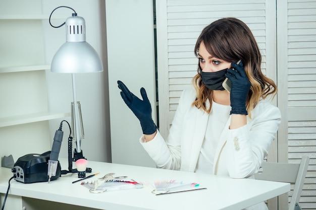 Jonge aantrekkelijke manicure professionele (meester van manicure) vrouw in een witte jas, masker en zwarte rubberen handschoenen praat aan de telefoon in een schoonheidssalon op de werkplek