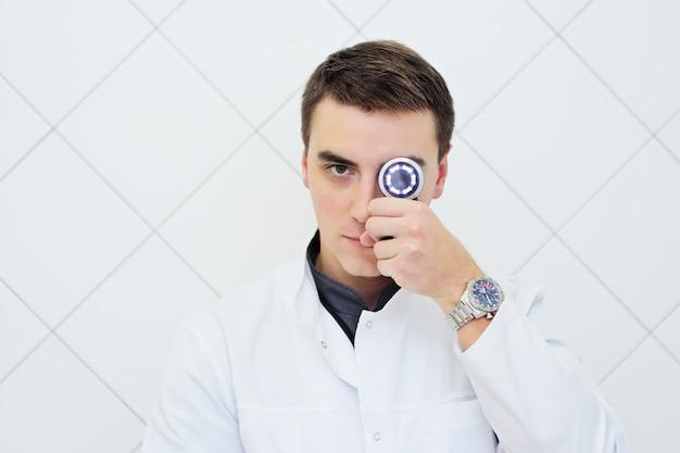 Jonge aantrekkelijke mannelijke artsendermatoloog met in hand dermatoscope