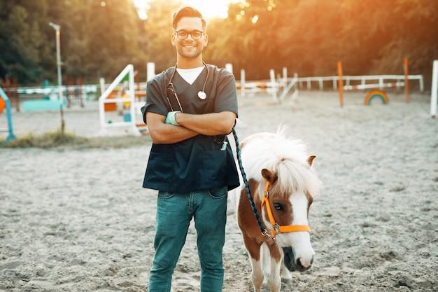 Jonge aantrekkelijke mannelijke dierenarts permanent en poseren met schattige kleine pony paard.