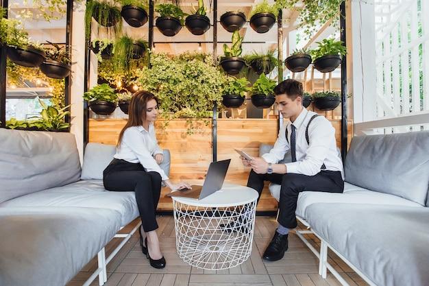 Jonge aantrekkelijke medewerkers op zakenvrouwen met een laptop in klassieke kleding.