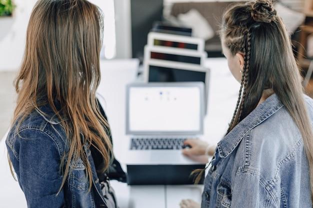Jonge aantrekkelijke meisjes in een elektronicawinkel gebruiken een laptop op een tentoonstelling. concept het kopen van gadgets.