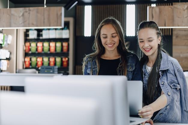 Jonge aantrekkelijke meisjes in een elektronicawinkel gebruiken een laptop op een tentoonstelling