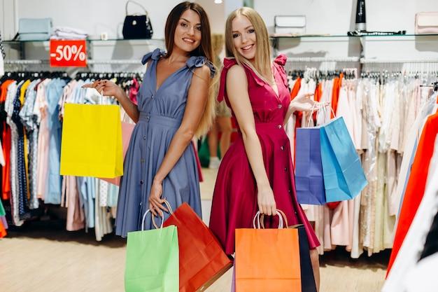 Jonge aantrekkelijke meisjes met boodschappentassen genieten van winkelen
