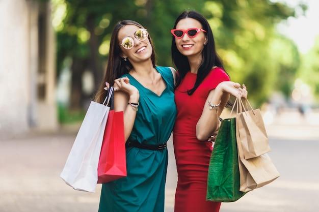 Jonge aantrekkelijke meisjes met boodschappentassen in de zomer stad. mooie vrouwen die in zonnebril camera en het glimlachen bekijken. positieve emoties en winkelen dag concept.