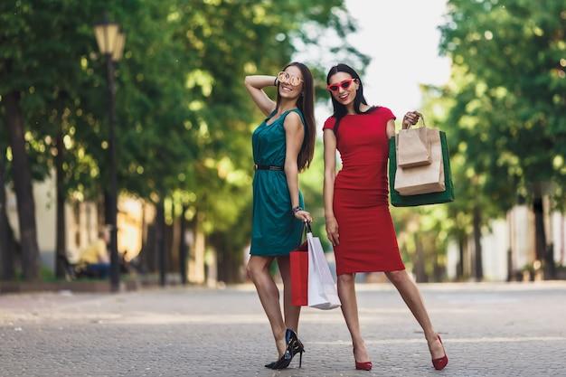 Jonge aantrekkelijke meisjes met boodschappentassen in de zomer stad. mooie vrouwen in zonnebril en glimlachen. positieve emoties en winkelen dag concept.