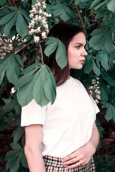 Jonge aantrekkelijke meisjes vrijetijdskleding op achtergrond van de bladeren van de kastanjeboom. concept van jeugd, levensstijl, natuurlijke schoonheid.