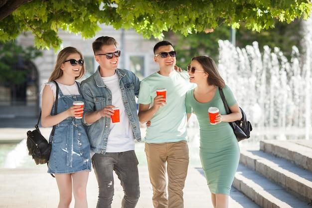 Jonge aantrekkelijke mensen plezier samen buitenshuis. mensen die koffie drinken en glimlachen. groep vrienden samen wandelen.
