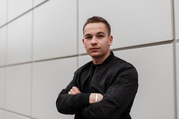 Jonge aantrekkelijke modieuze man in stijlvol zwart in een lichte jas voorjaar vormt in de buurt van de moderne muur op een warme lentedag in de stad.