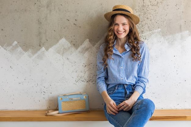 Jonge aantrekkelijke modieuze vrouwenzitting bij muur