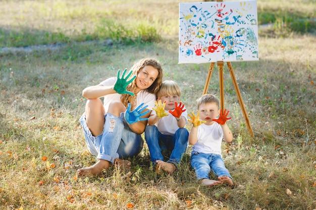 Jonge aantrekkelijke moeder die pret met haar kinderen heeft bij het park. vrolijke familie plezier buiten. mam speelt met haar kinderen.