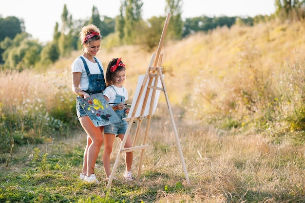 Jonge aantrekkelijke moeder leert dochter schilderen in zomer park. buiten activiteit voor het concept van schoolgaande kinderen