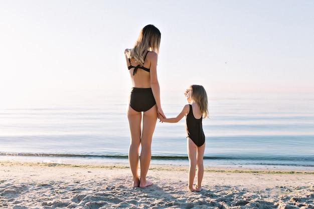 Jonge aantrekkelijke moeder met mooie dochtertje gekleed in zwarte zwempakken op het strand van de zomer