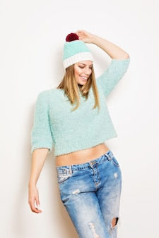 Jonge aantrekkelijke mooie gelukkige vrouw in fuzzy bijgesneden mintgroene trui en bijpassende kleur gebreide muts en denim jeans poseren op witte achtergrond