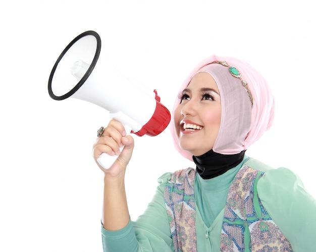 Jonge aantrekkelijke moslimvrouw die gebruikend megafoon schreeuwt
