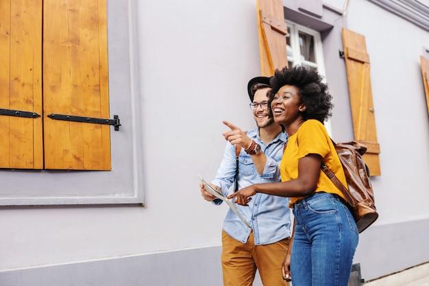 Jonge aantrekkelijke multiculturele toeristen lopen op straat en kijken naar prachtige gebouwen. vrouw wijzend op kaart terwijl man op iets wijst.