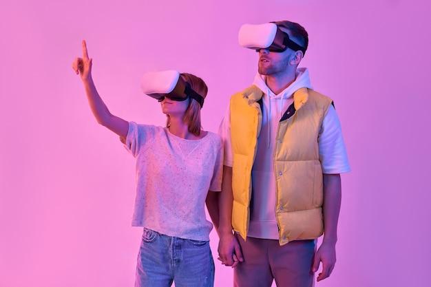 Jonge aantrekkelijke paar in vrijetijdskleding, hand in hand, virtual reality-bril gebruiken