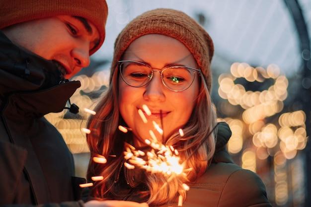 Jonge aantrekkelijke paar knuffel en kus buiten met de wonderkaarsen in hun handen nieuwjaar vieren