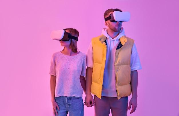 Jonge aantrekkelijke paar man en vrouw in vrijetijdskleding, hand in hand, virtual reality-bril gebruiken