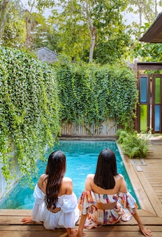 Jonge aantrekkelijke paar ontspannen bij een zwembad in een tropische tuin