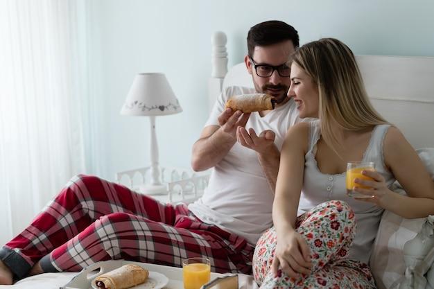 Jonge aantrekkelijke paar samen ontbijten in bed
