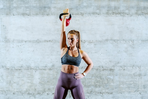 Jonge aantrekkelijke pasvorm kaukasische sportvrouw in sportkleding met paardenstaart die zich met één hand op heup bevindt en de klok van de ketel opheft.