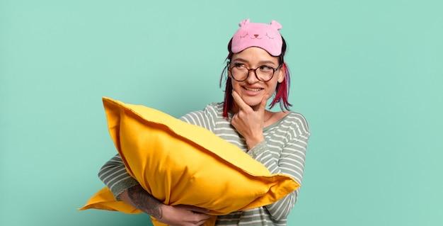 Jonge aantrekkelijke rode haarvrouw die met een gelukkige, zelfverzekerde uitdrukking met hand op kin glimlacht, zich afvraagt en naar de kant kijkt en pyjama draagt.