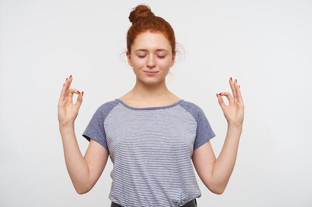 Jonge aantrekkelijke roodharige dame met natuurlijke make-up verhogen handen in mudra gebaar en houdt haar ogen gesloten terwijl ze over een witte muur staat