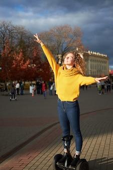 Jonge aantrekkelijke roodharige gekrulde fit vrouw met gesloten ogen rijden op hoverboard in de straat