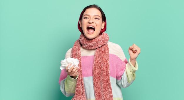Jonge aantrekkelijke roodharige vrouw agressief schreeuwen met een boze uitdrukking of met gebalde vuisten vieren succes griep concept