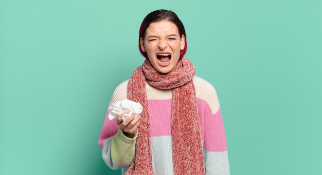 Jonge aantrekkelijke roodharige vrouw die agressief schreeuwt, erg boos, gefrustreerd, verontwaardigd of geïrriteerd kijkt, geen griepconcept schreeuwt