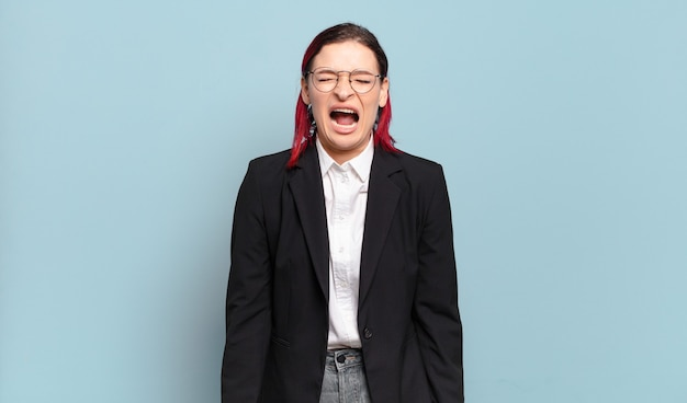 Jonge aantrekkelijke roodharige vrouw die agressief schreeuwt