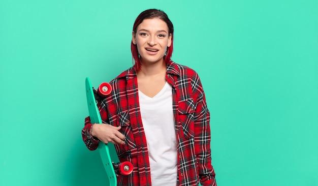 Jonge aantrekkelijke roodharige vrouw die blij en aangenaam verrast kijkt, opgewonden met een gefascineerde en geschokte uitdrukking en een skateboard vasthoudt