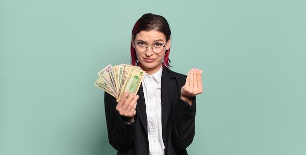 Jonge aantrekkelijke roodharige vrouw die capice of geldgebaar maakt en u vertelt uw schulden te betalen!. geld concept