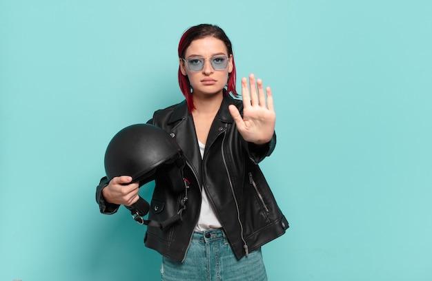 Jonge aantrekkelijke roodharige vrouw die er serieus, streng, ontevreden en boos uitziet en een open palm laat zien die een stopgebaar maakt. motorrijder concept
