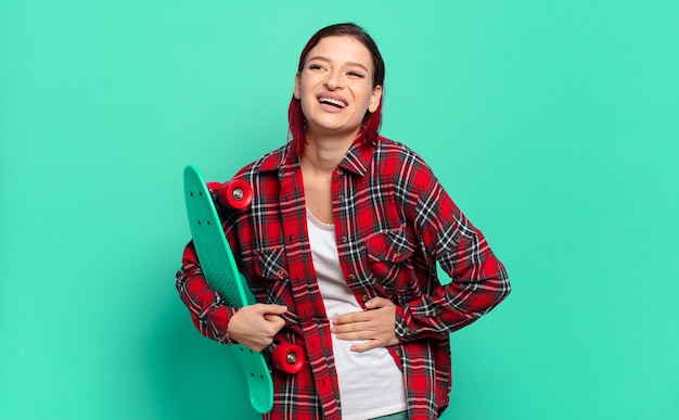 Jonge aantrekkelijke roodharige vrouw die hardop lacht om een hilarische grap, zich gelukkig en opgewekt voelt, plezier heeft en een skateboard vasthoudt