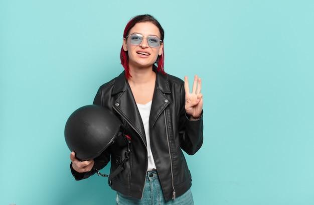 Jonge aantrekkelijke roodharige vrouw die lacht en er vriendelijk uitziet, nummer drie of derde toont met de hand naar voren, aftellend. motorrijder concept