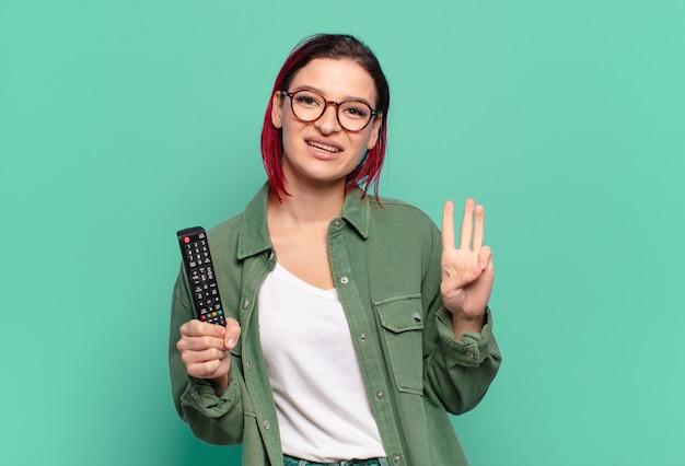 Jonge aantrekkelijke roodharige vrouw die lacht en er vriendelijk uitziet, nummer drie of derde toont met de hand naar voren, aftelt en een tv-afstandsbediening vasthoudt