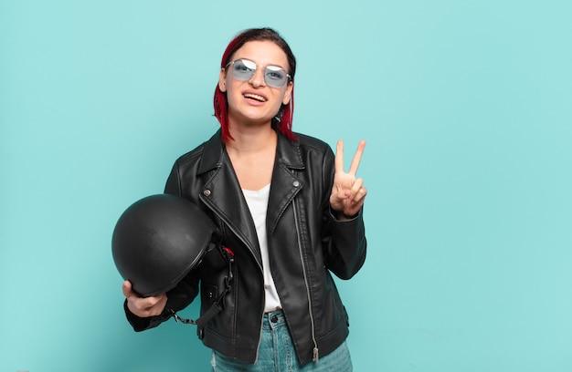 Jonge aantrekkelijke roodharige vrouw die lacht en er vriendelijk uitziet, nummer twee of seconde toont met de hand naar voren, aftellend. motorrijder concept