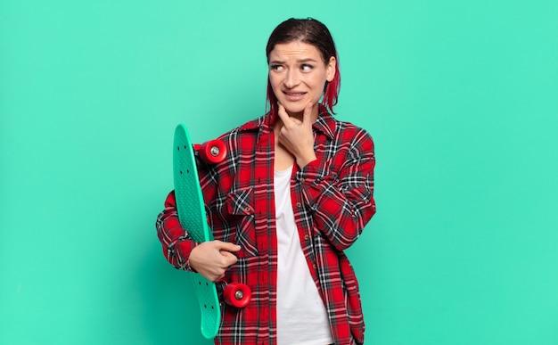 Jonge aantrekkelijke roodharige vrouw die lacht met een gelukkige, zelfverzekerde uitdrukking met de hand op de kin, zich afvragend en naar de zijkant kijkt en een skatebord vasthoudt