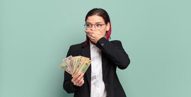 Jonge aantrekkelijke roodharige vrouw die mond bedekt met handen met een geschokte, verbaasde uitdrukking, een geheim bewaren of oeps zeggen. geld concept