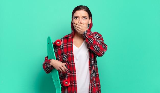 Jonge aantrekkelijke roodharige vrouw die mond bedekt met handen met een geschokte, verbaasde uitdrukking, een geheim houdt of oeps zegt en een skatebord vasthoudt
