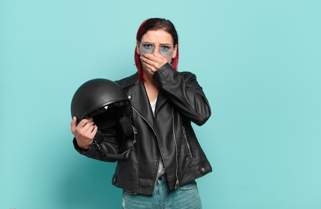 Jonge aantrekkelijke roodharige vrouw die mond bedekt met handen met een geschokte, verbaasde uitdrukking, een geheim houdt of oeps zegt. motorrijder concept
