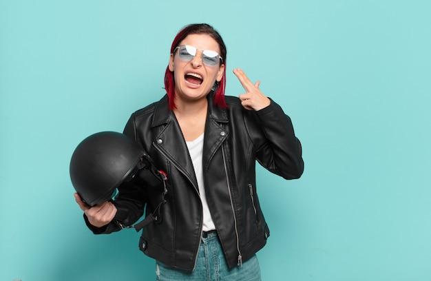 Jonge aantrekkelijke roodharige vrouw die ongelukkig en beklemtoond kijkt, zelfmoordgebaar die pistoolteken maakt met hand, die naar hoofd wijst. motorrijder concept