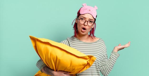 Jonge aantrekkelijke roodharige vrouw die verrast en geschokt kijkt, met open mond terwijl ze een object vasthoudt met een open hand aan de zijkant en een pyjama draagt