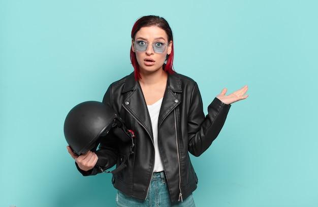 Jonge aantrekkelijke roodharige vrouw die verrast en geschokt kijkt, met open mond terwijl ze een object vasthoudt met een open hand aan de zijkant. motorrijder concept